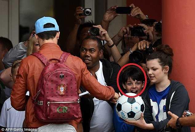 Một cậu bé phấn khích với phần quà là trái bóng có chữ kí của siêu sao người Bồ Đào Nha