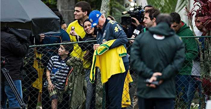 HLV Scolari tranh thủ ra hàng rào ký tặng các fan hâm mộ tới theo dõi ĐT Brazil tập.