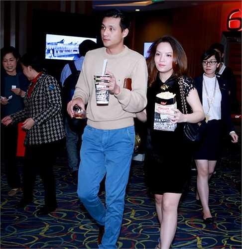 Hai vợ chồng tay trong tay tình cảm tại rạp chiếu phim.