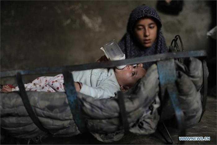 Hình ảnh cô bé 12 tuổi, Tagreed Abu Shaweesh, đang cho em gái 4 tháng tuổi uống những giọt sữa quý tại nhà ở thành phố Gaza, Palestines.