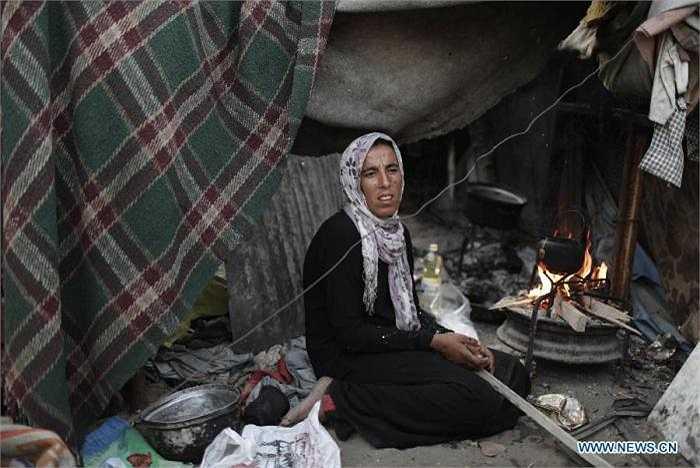 Bà mẹ Naeema Abu Shaweesh, 30 tuổi, với khuôn mặt khắc khổ đang chuẩn bị pha trà bên bếp lửa.