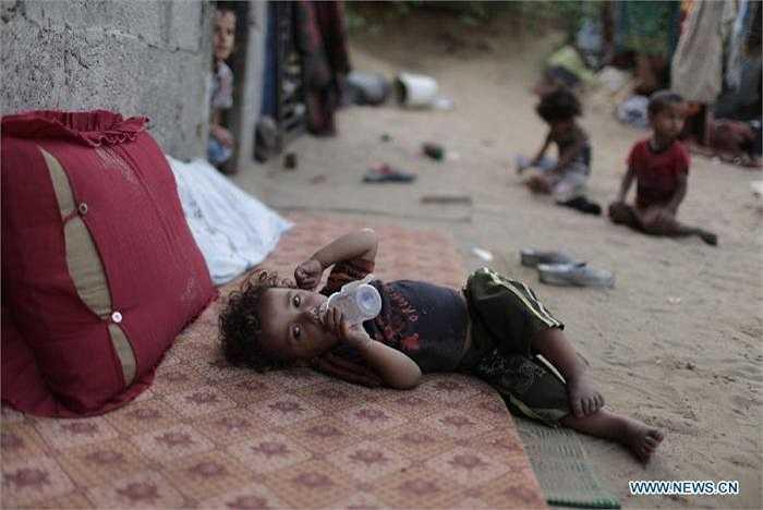 Em bé Wael Abu Shaweesh, 2 tuổi, ngậm  bình sữa trống rỗng nằm lê lết giữa nhà.