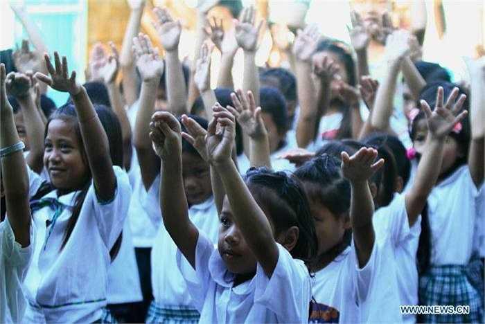 Với nụ cười rạng rỡ, các em học sinh hăng hái giơ tay trong ngày khai giảng năm học mới.