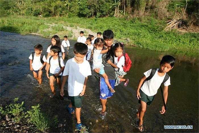 Một người đàn ông đang giúp các học sinh nhỏ này băng qua mộc con sông để đến trường.