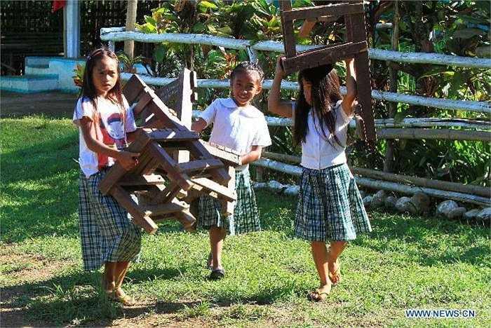 Các bé gái cùng nhau vác ghế để tham dự lớp học.
