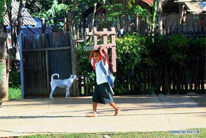 Cậu nhóc cười rạng rỡ, hăng hái mang theo chiếc ghế từ nhà đến trường.