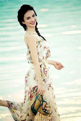 Hoa hậu du lịch Ngọc Diễm diện váy in họa tiết hoa duyên dáng khi thả bộ trên bờ biển.