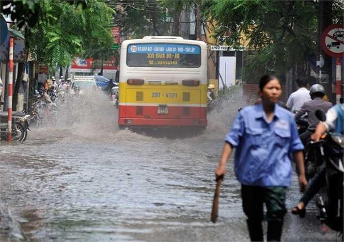 Trong khoảng ba giờ đồng hồ nước chưa thoát hết, xe buýt đi qua tạo thành hai làn sóng đánh sang hai bên đường khiến nhiều người đi xe máy bị nước bắn vào ướt sũng - Ảnh: Zing