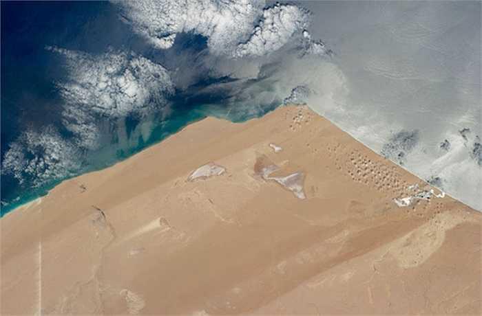 Bờ Bờ Đại Tây Dương khô cằn ở khu vực Tây Phi, cùng sự phản chiếu của tia nắng mặt trời trên đại dương và các phá nước mặn (hay còn được gọi là sabkha). Ảnh chụp từ Trạm Vũ trụ Quốc tế ISS.