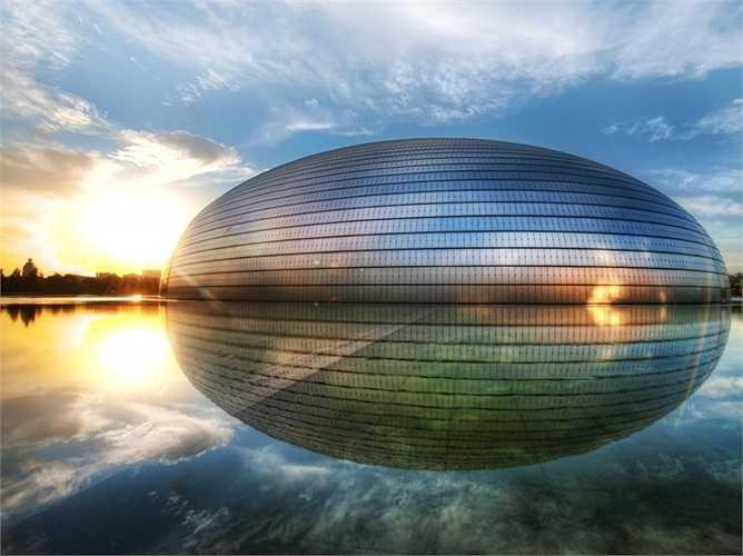 """Đây là lý do tại sao Nhà hát lớn quốc gia ở Bắc Kinh, Trung Quốc lại có tên là """"The Egg"""" (Quả trứng). Tòa nhà được cấu tạo bởi titanium và kính nằm giữa một chiếc hồ nhân tạo. Vì hình dạng đặc biệt này mà nhà hát còn được gọi là 'quả trứng' hay 'ốc đảo pha lê'."""