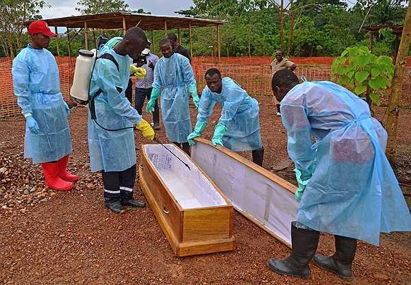 Đội an táng đang tiến hành khử trùng một chiếc quan tài để chuẩn bị án táng một nạn nhân nhiễm Ebola ở Kailahun.