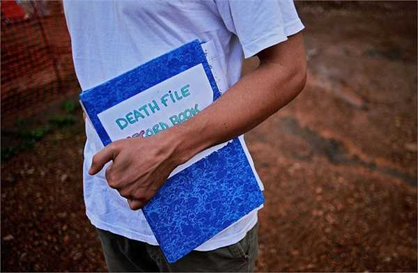 Một nhân viên của tổ chức Bác sỹ không biên giới cầm cuốn sách ghi lại chi tiết cái chết của các bệnh nhân mắc Ebola.