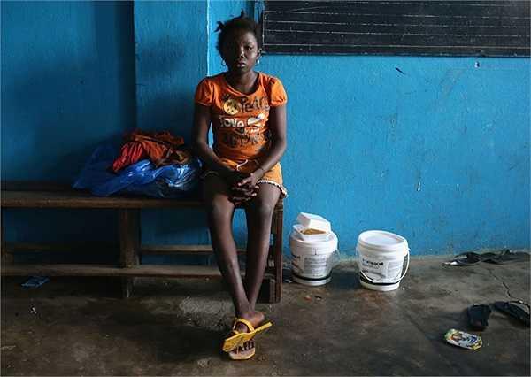 Sowe, 15 tuổi, ngồi một mình trong phòng học, được sử dụng làm nơi cách ly cho những người chưa nhiễm Ebola tại Liberia.