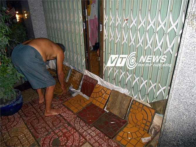Dùng gạch che chắn hạn chế nước tràn vào nhà. Ảnh: Phan Cường