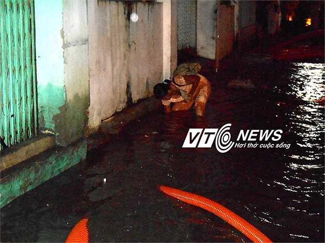 Một phụ nữ mò tìm đồ bị rơi giữa dòng nước. Ảnh: Phan Cường