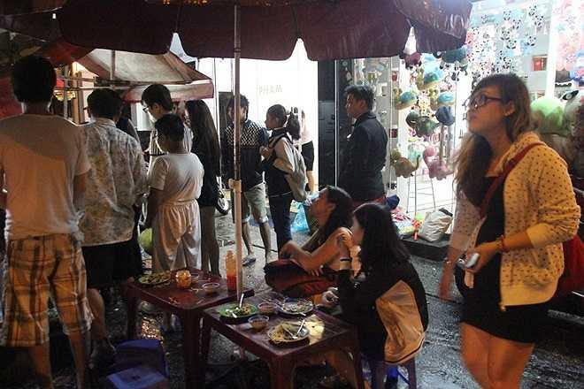 Dưới lòng đường khách mặc áo mưa chờ, trên vỉa hè mọi người cũng chờ đến lượt mình được mua hàng. Không ai cảm thấy bực bội vì phải đứng chờ ít nhất 20 phút mới mua được đồ ăn.