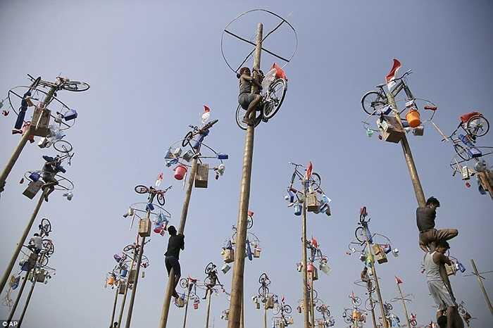 Những người đàn ông trèo lên đỉnh cột mỡ