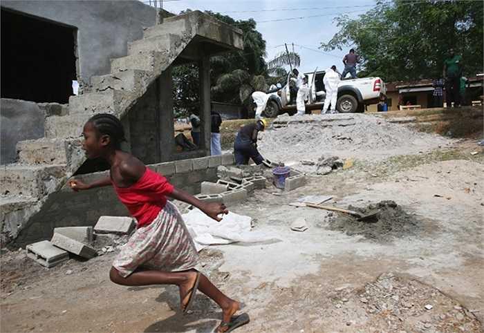 Một cô gái hoảng sợ và bỏ chạy khi đội mai táng chuẩn bị thu nhặt thi thể của một người phụ nữ chết vì virus Ebola