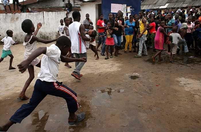 Một người đàn ông đưa bé gái ra khỏi trung tâm cách ly giữa đám đông đang tản ra để né tránh ở khu ổ chuột West Point
