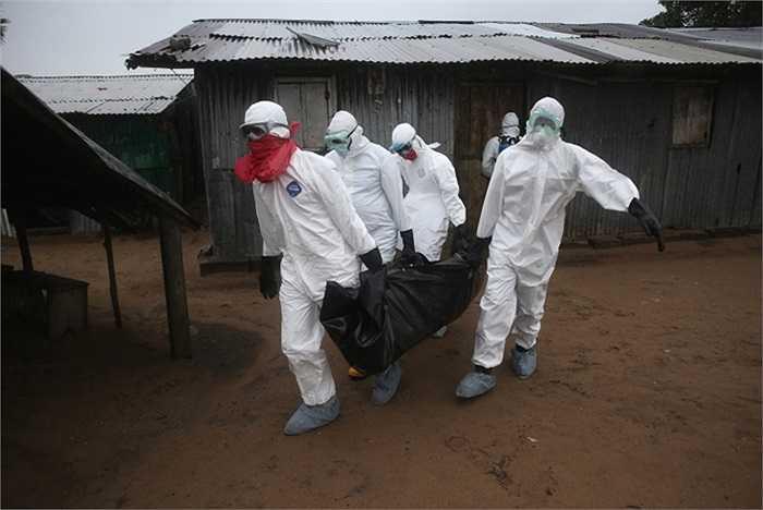 Một nhóm chôn cất Liberia mặc quần áo bảo vệ đưa thi thể của một nạn nhân 60 tuổi bị nhiễm Ebola ra khỏi nhà