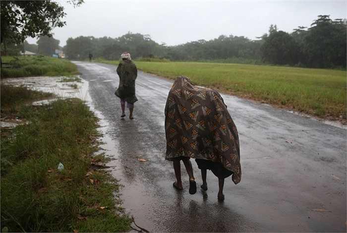 Hanah Siafa đi bộ trong mưa cùng 2 cô con gái Josephine 10 tuổi và Elija 6 tuổi.