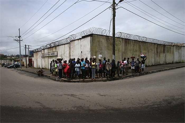 Người dân địa phương đứng nghe các nhân viên  y tế tuyên truyền giúp nâng cao nhận thức về Ebola