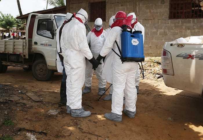 Một đội chôn cất của Bộ y tế Liberia nắm tay nhau cùng cầu nguyện trước khi bước vào một ngôi nhà để di chuyển thi thể của một người phụ nữ chết vì virus Ebola.