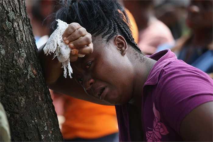 Korpo Klay đau đớn nhìn đội chôn cất của Bộ Y tế Liberia vào nhà người em họ Kormassa Kaba của cô, người đã chết vì virus Ebola.