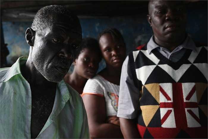 Người dân đứng nhìn cậu bé từ biệt cha mình trước khi đến trung tâm cách ly dịch bệnh Ebola