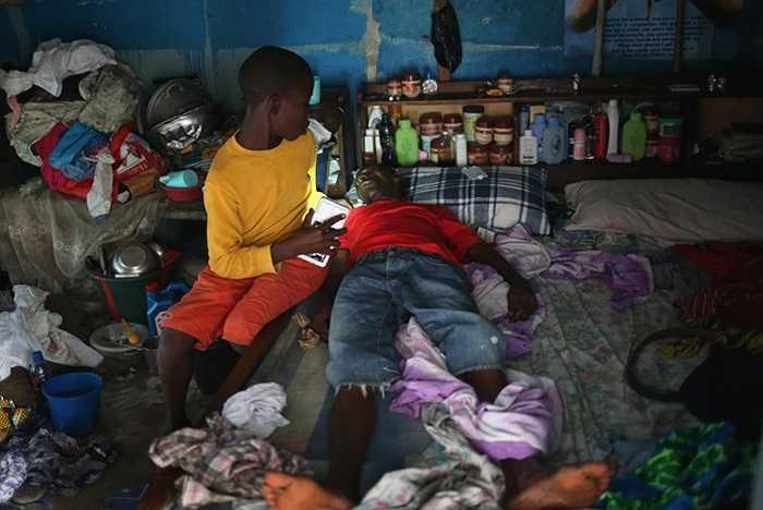 Một cậu bé chăm sóc cha mình trước khi họ được đưa đến khu cách ly dịch bệnh Ebola