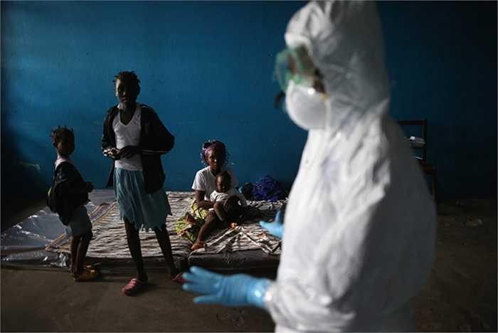 Một nhân viên y tế nói chuyện với các gia đình trong một phòng học được sử dụng làm khu cách ly Ebola