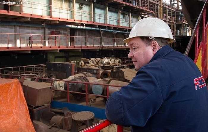 Trong ảnh là một công nhân vịn vào lan can chiếc thang của tàu