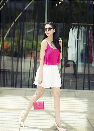 Ngọc Trinh nổi bật trên phố khi mặc váy trắng, áo hồng, đeo túi cùng màu áo.