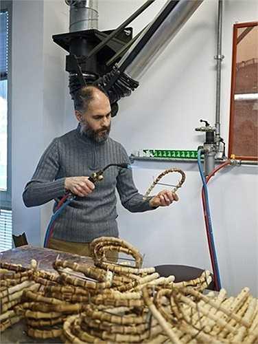 Người thợ thủ công đang chế tác những chiếc tay cầm túi xách bằng tre.
