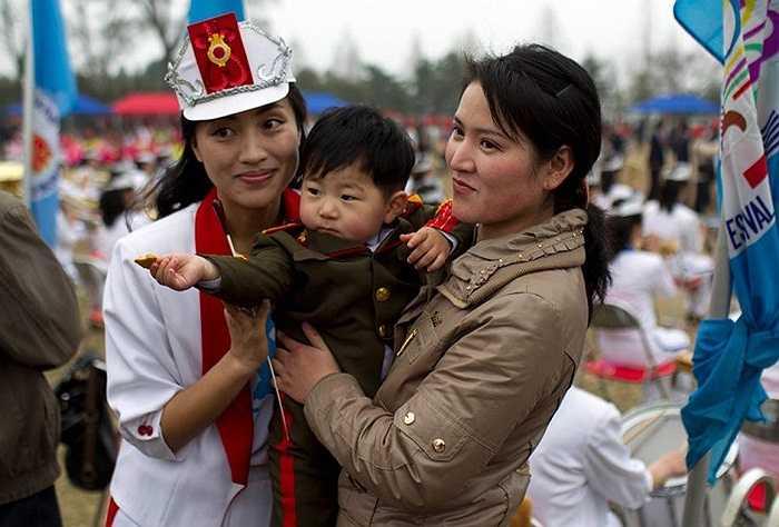 Một nữ nhân viên trong đội tuần hành đường phố chụp ảnh với cậu bé bên đường ở Bình Nhưỡng