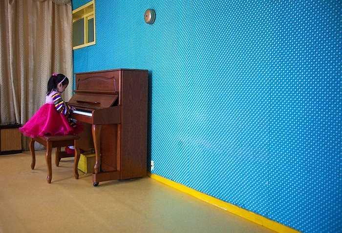 Một em nhỏ chơi đàn Piano ở trong lớp học Bình Nhưỡng
