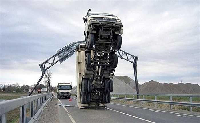 Trong ảnh là chiếc xe tải quên hạ ben, mắc kẹt 'chổng vó' trên một con đường tại Trung Quốc. Chỗ mắc kẹt chính là bảng phân chia làn luồng, giới hạn tốc độ, chiều cao tĩnh không...thường được dựng lên trên các tuyến cao tốc.