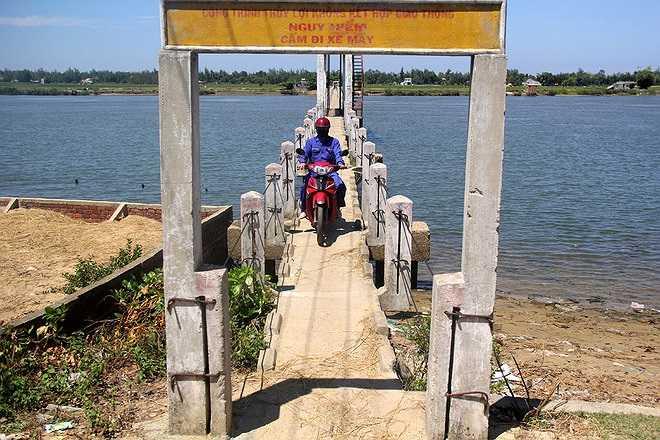 Vì là đường dẫn nước nên chiều ngang của cây cầu chỉ là 0,8 m, đủ cho hai người đi bộ tránh nhau. Dù có biển cấm xe máy, người dân 2 xã Tam Tiến và Tam Xuân 2 vẫn hàng ngày phóng xe qua lại.