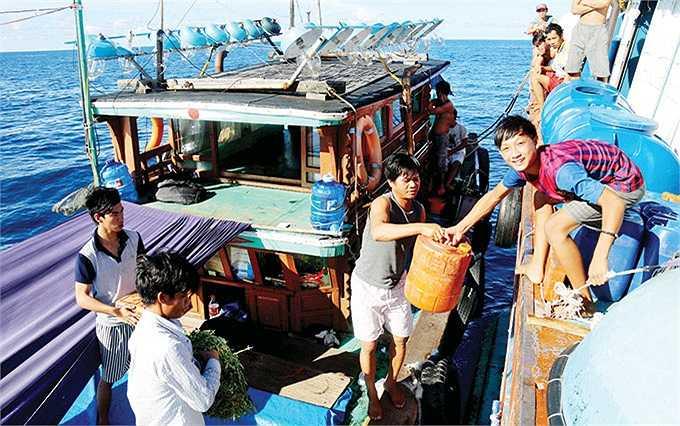 Em Mai Văn Phúc (16 tuổi, phải), anh nuôi của tàu cá QB 91754, nhận rau xanh, thịt và mì gói từ tàu hậu cần TTH 95527.