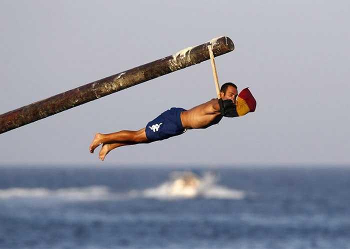 Một người đàn ông trượt khỏi cột mỡ, trong kỷ niệm lễ tôn giáo Thánh Julian kéo dài một tuần, bên ngoài Valletta, Malta