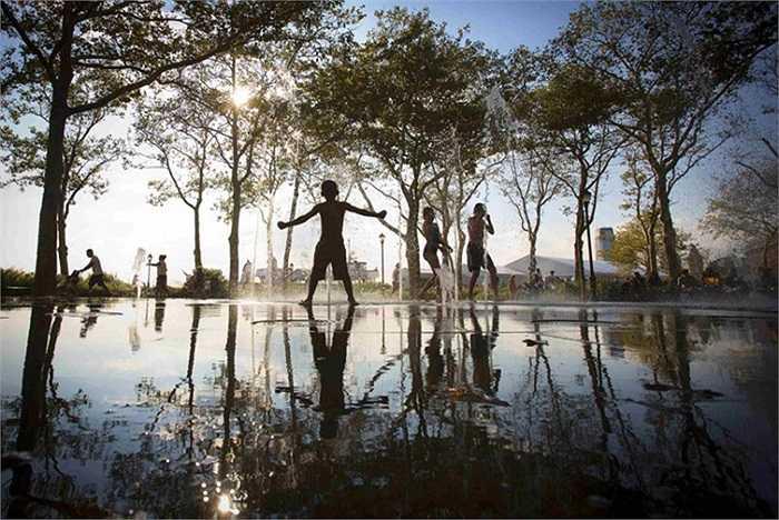 Trẻ em chơi đùa trong đài phun nước ở quận Lower Manhattan của New York