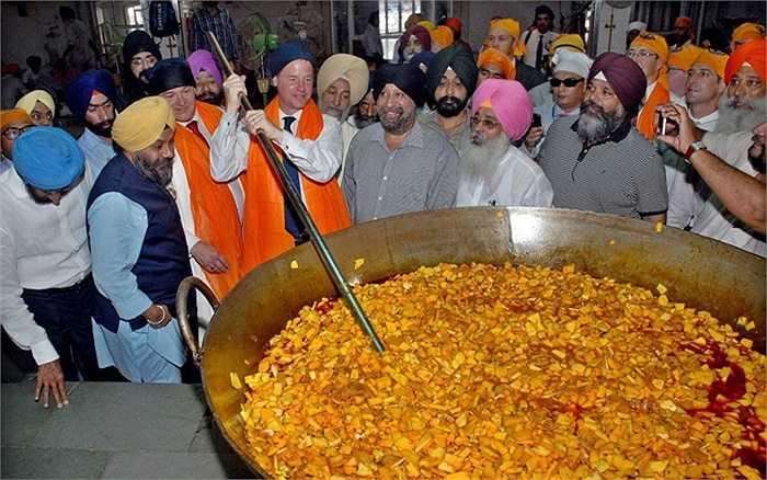 Phó Thủ tướng Ấn Độ Nick Clegg trộn chảo rau khi đến thăm một ngôi đền