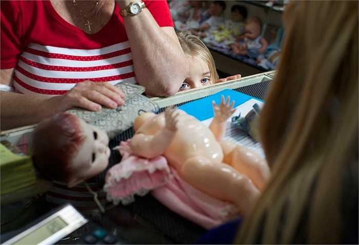Một khách hàng trẻ cùng gia đình đem búp bê bị hỏng đến bệnh viện sữa chữa