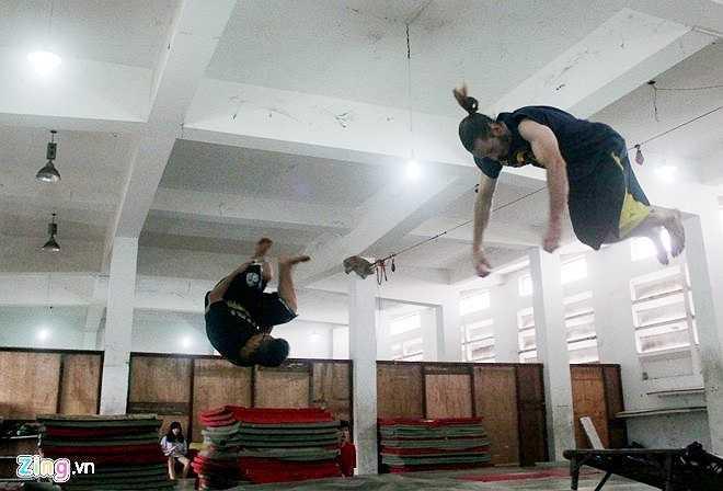 Vy Thành, người đã có 7 năm tập môn thể thao mạo hiểm này chia sẻ, các bạn trong nhóm chủ yếu tập các động tác được gọi là Tricking (dậm nhảy từ giá dây cao su bay lên lộn vòng và tiếp đất xuống đệm), Backflin (xoay người và bật nhảy từ dưới đất lên không trung), nhảy vượt địa hình và nhảy các động tác tự do. Trong ảnh, hai thành viên nhảy động tác Tricking, bay người lên cao và lộn nhiều vòng.