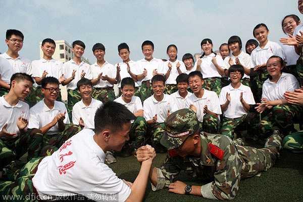 Sinh viên năm thứ nhất và sĩ quan thi đấu vật tay trước sự cổ vũ của đám đông sinh viên. Hình ảnh được chụp tại một trường học tại Trùng Khánh.