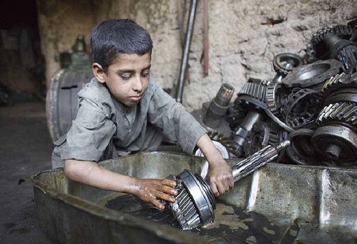 Một bé trai Afghanistan đang làm việc tại một cơ sở sửa xe.
