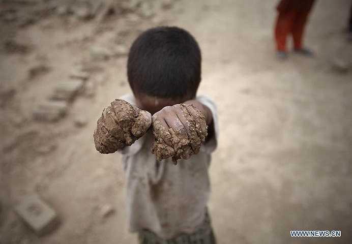 Hình ảnh một lao động nhí giơ bàn tay lấm lem bùn đất trong giờ làm việc tại xưởng gạch.