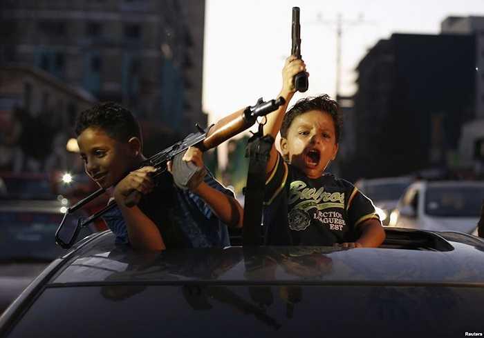 Trẻ em người Palestine giơ súng ăn mừng ở Thành phố Gaza sau một thỏa thuận ngừng bắn với Israel