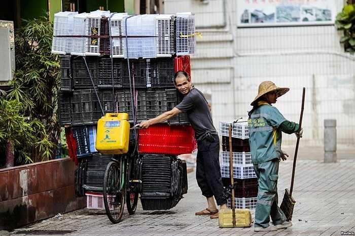 Người đàn ông đẩy chiếc xe đạp chất đầy những hộp nhựa trên đường phố tại Quảng Châu, tỉnh Quảng Đông, Trung Quốc