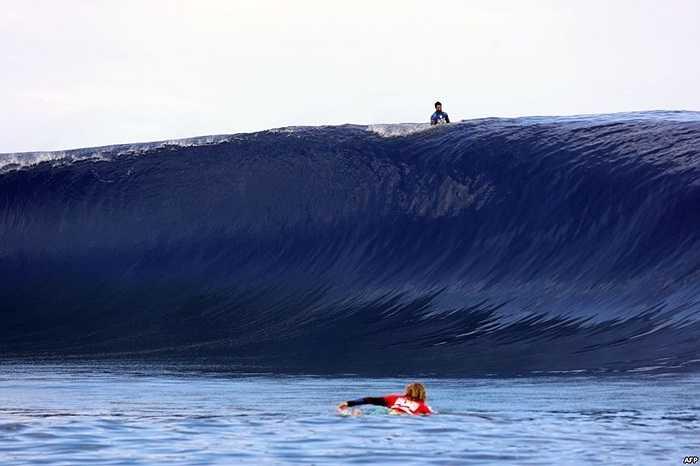 Kai Otton của Australia bơi bên dưới con sóng trong khi Dion Atkinson của Australia lướt bên trên trong ngày trình diễn cuối cùng của sự kiện lướt sóng ở quần đảo Polynesia